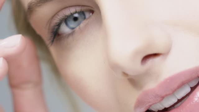 vídeos de stock e filmes b-roll de smiling woman with blue eyes touching her skin - mulher bonita