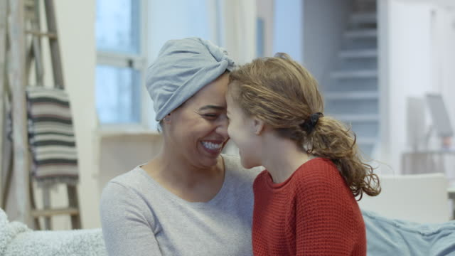Smiling woman with cancer embraces her daughter A black woman with cancer is spending time with her daughter. The woman is wearing a headscarf to hide her hair loss from chemotherapy treatment. The mother is holding her daughter. The two individuals are smiling and leaning in close with their foreheads touching. cancer patient stock videos & royalty-free footage