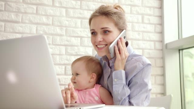 Femme souriante avec enfant parlant de téléphone. Mère heureuse entreprise travaillant à domicile - Vidéo