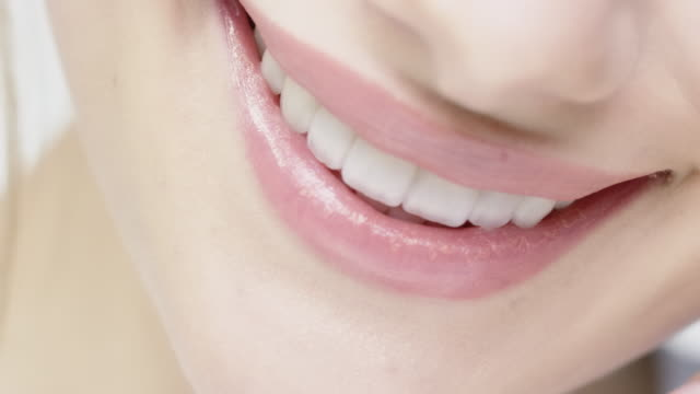 smiling woman with glossy lips and blue eyes - sorriso aperto video stock e b–roll