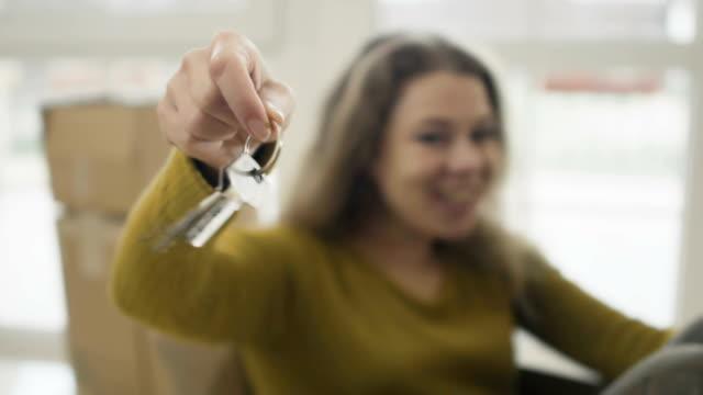 leende kvinna med nycklar från ett nytt hus - hänga bildbanksvideor och videomaterial från bakom kulisserna