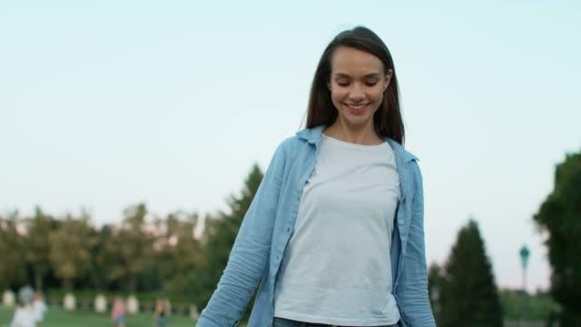 夏の公園で歩くショッピングバッグと笑顔の女性。ハッピーウーマン ビデオ