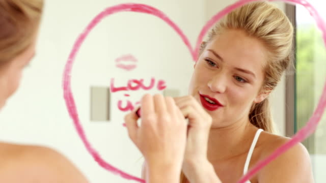 Smiling woman writing love words on the mirror video