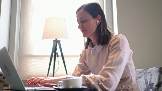 stockvideo's en b-roll-footage met glimlachende vrouwen beantwoorden aan een sms-bericht tijdens het werken op haar laptop weg van huis - ver