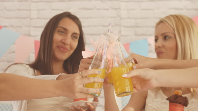 smiling women toasting with juices at baby shower party. - baby shower stock videos and b-roll footage