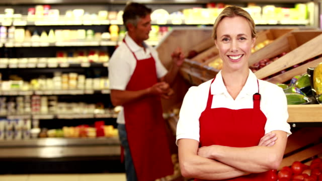 Smiling worker in front of her colleague Portrait of smiling worker in front of her colleague in grocery store christmas stocking stock videos & royalty-free footage
