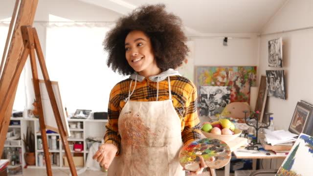 vídeos y material grabado en eventos de stock de sonriente joven afro mujer sosteniendo paleta de colores y pincel - pintor artista