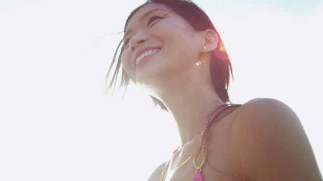 vidéos et rushes de souriante jeune asiatique chinoise femelle surfeur sur la plage - évasion du réel