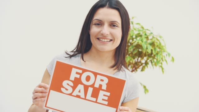 Smiling young beautiful woman is holding a plate with words FOR SALE written on it, offering house for sale and moving out.