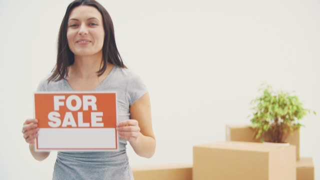 Smiling young beautiful woman is holding a plate with words FOR SALE written on it, giving thumb up.