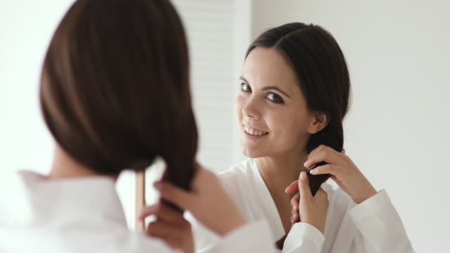 Smiling young beautiful woman touching healthy hair looking in mirror