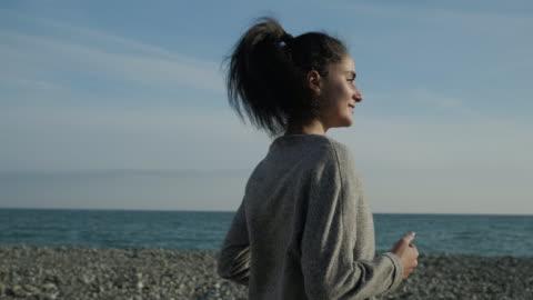 sorridente giovane bruna sta facendo jogging da solo in spiaggia soleggiata in primavera, - capelli castani video stock e b–roll