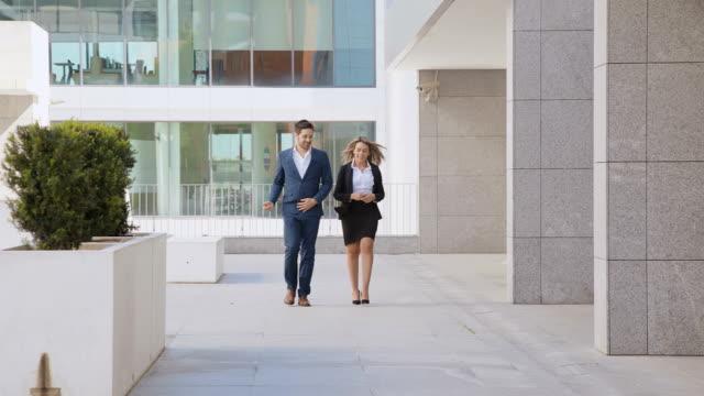 vídeos y material grabado en eventos de stock de jóvenes colegas de negocios sonrientes caminando al aire libre - bien vestido