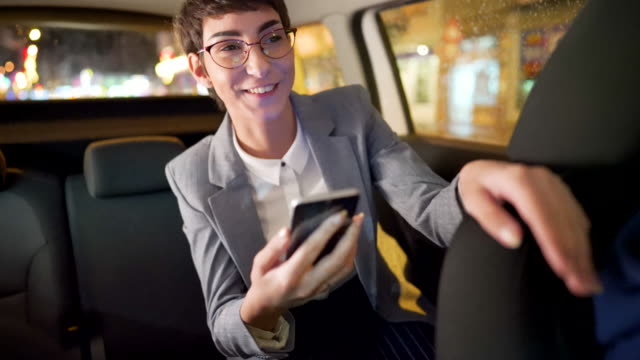 Smiling young businesswoman with a location on her phone navigates the car driver