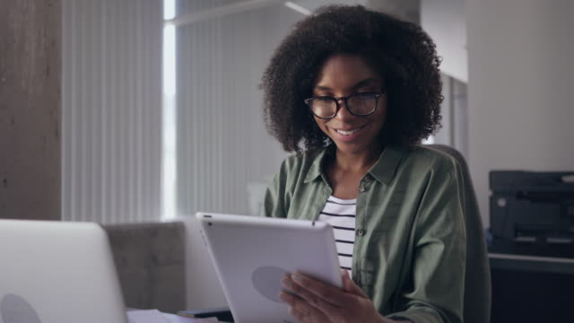 Smiling young confident businesswoman using digital tablet