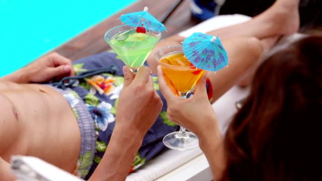 lächelnd junges paar rösten getränke - tropischer cocktail stock-videos und b-roll-filmmaterial