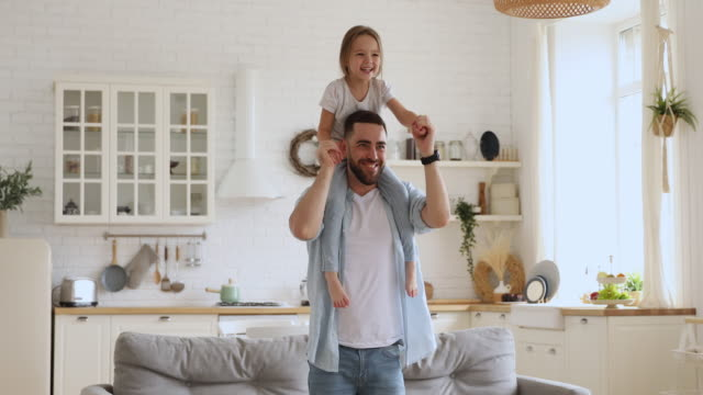 Smiling young daddy carrying excited little daughter, dancing together.