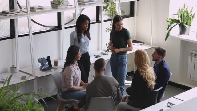 vídeos de stock, filmes e b-roll de sorrindo jovens falantes diversos envolvendo companheiros de equipe na atividade de formação de equipe. - ambiente evento