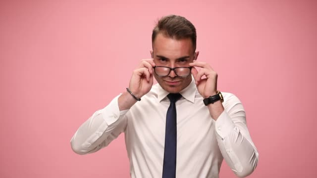 smiling young fashion man in white shirt wearing glasses crossing arms posing looking over glasses on pink background