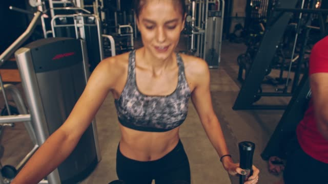 vídeos de stock e filmes b-roll de smiling young female athlete enjoying her workout on elliptical machine - aparelho de musculação