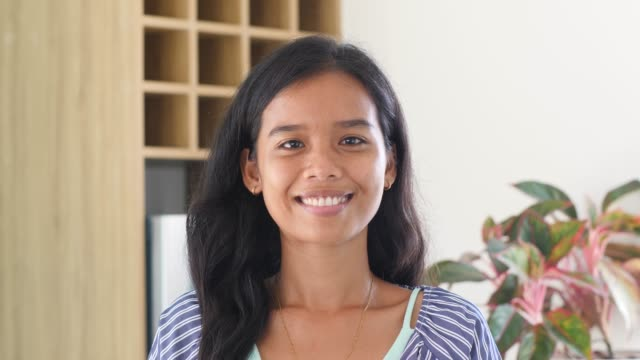 Smiling young Filipino woman small face looking at the camera posing at home Smiling young Filipino woman pretty small face looking at the camera posing alone at home. happy millennial Asian ethnicity girl student professional close up front portrait filipino ethnicity stock videos & royalty-free footage