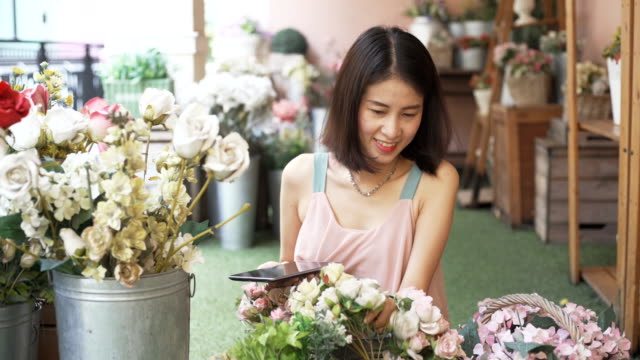 smiling young florist business woman at flower shop making and working decorations and arrangements floral for order and flowers delivery. small business owner - owner laptop smartphone video stock e b–roll