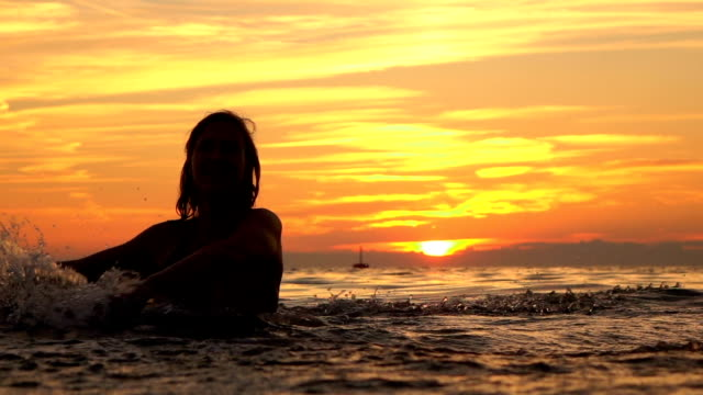 slow motion: smiling young girl playing with water in ocean at golden sunset - pesche bambino video stock e b–roll