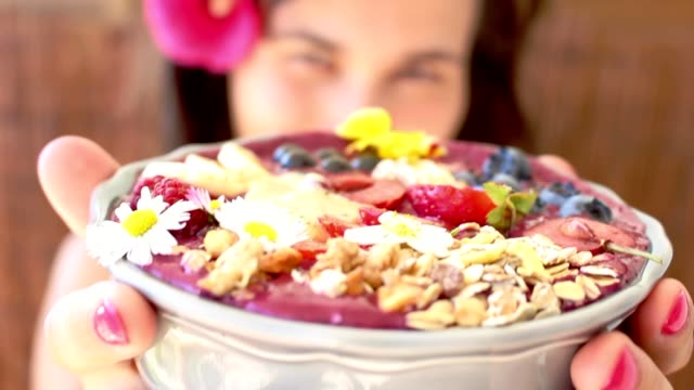 smiling, young girl, woman giving, showing bowl with acai berry fruits video