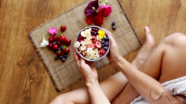 vídeos de stock e filmes b-roll de smiling, young girl, woman giving, showing bowl with acai berry fruits to the camera - oats