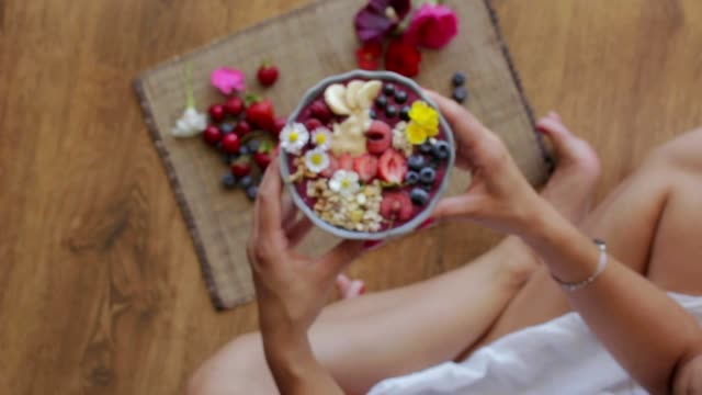 smiling, young girl, woman giving, showing bowl with acai berry fruits to the camera video