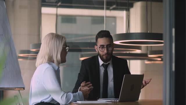 stockvideo's en b-roll-footage met glimlachende jonge mannelijke arabische financiële adviseur die midden oude onderneemster raadpleegt. - partnership