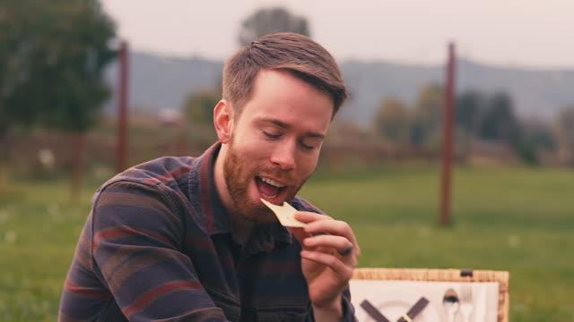 lächelnder junger mann essen käse bei einem picknick auf einer herbst tag - käse stock-videos und b-roll-filmmaterial