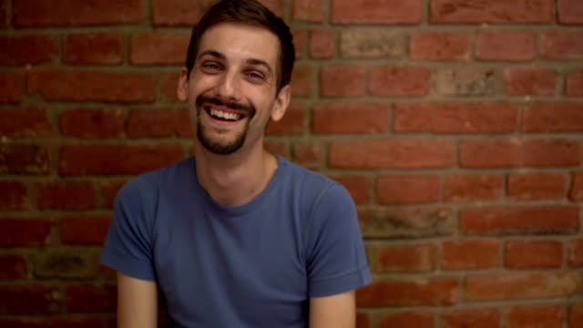 smiling young man in front of a brick wall - miroslav mitic stock videos and b-roll footage