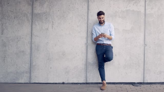 Smiling young man leaning against wall and texting on smartphone Smiling young man leaning against wall and texting on smartphone leaning stock videos & royalty-free footage