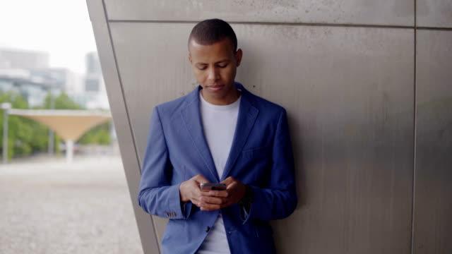stockvideo's en b-roll-footage met glimlachende jonge man leunend op de muur en het gebruik van smartphone. - hangen