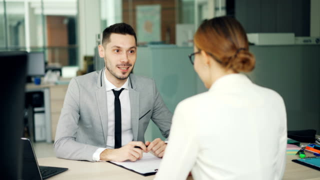 Smiling young man recruiter is talking to young woman successful candidate then shaking her hand during job interview in office. People and work concept. Smiling young man recruiter is talking to young woman successful candidate then shaking her hand during job interview in office. People, conversation and work concept. job interview stock videos & royalty-free footage