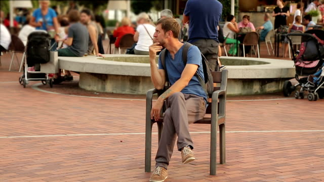 Smiling young man sitting on chair in park, making funny video