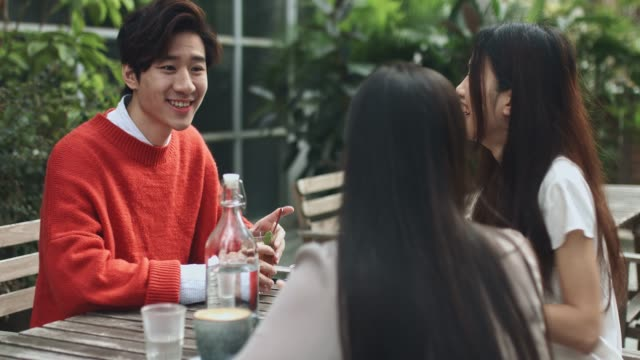smiling young man talking with friends at cafe - terrazza video stock e b–roll