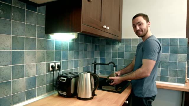 Sonriente joven lavando platos y hablando a la cámara - vídeo