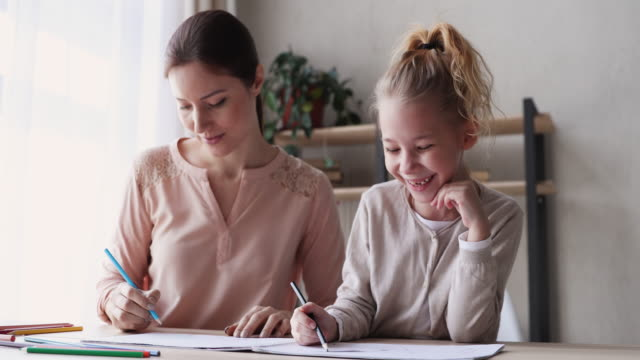Smiling young mother drawing pictures in album with daughter.