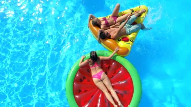 AERIAL: Smiling young people in pool having water fight on fun inflatable floats AERIAL: Cheerful friends having water gun fight on colorful floaties at pool party. Playful guys and girls splashing water and having fun on inflatable pizza, doughnut, flamingo and watermelon floats pool party stock videos & royalty-free footage