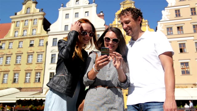 Smiling Young People Standing on the Old City Square. Cute Brunette Using Smartphone and Touching a Screen Showing Something to Her Friends video