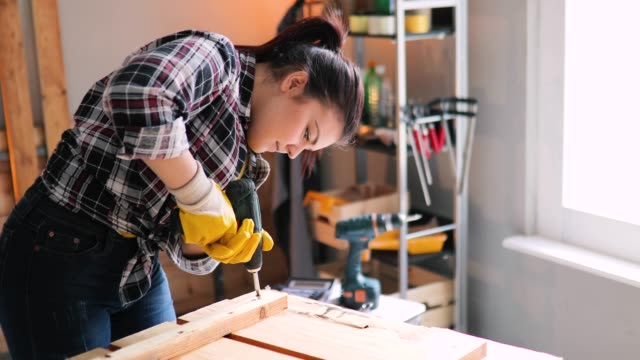smiling young professional female carpentry worker with electric screwdriver on the table in the workshop smiling young professional female carpentry worker with electric screwdriver on the table in the workshop timber stock videos & royalty-free footage