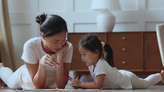 Smiling young vietnamese mother drawing pictures with cute daughter.