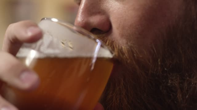 A Smiling Young White Man with a Red Beard Drinks a Beer A Caucasian man in his twenties with blue eyes and a red beard take a sip of his frothy beer as he smiles. bar counter stock videos & royalty-free footage