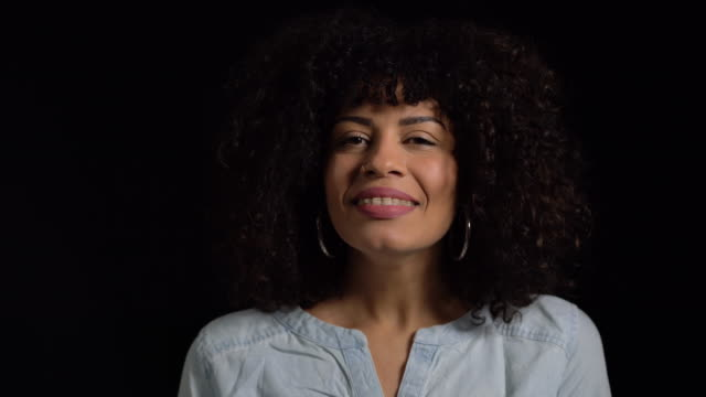 Smiling young woman against black background Close-up of young woman breathing deeply against black background. Lockdown shot of female is wearing casuals. She is having short curly hair. deep stock videos & royalty-free footage