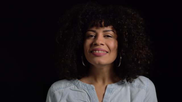 lächelnde junge frau vor schwarzem hintergrund - atemübung stock-videos und b-roll-filmmaterial