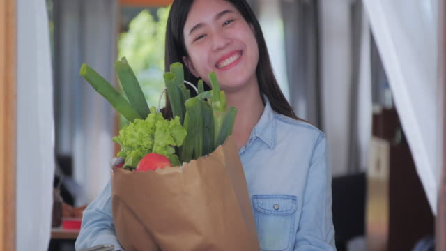 smiling young woman and holding a bag full of healthy food in the kitchen. having fun while making food for healthy,body-positive women - stay at home parent stock videos & royalty-free footage
