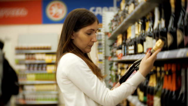 Smiling young woman choosing a bottle of red wine.