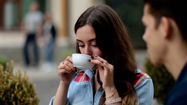 Smiling young woman drinking coffee at cafe video